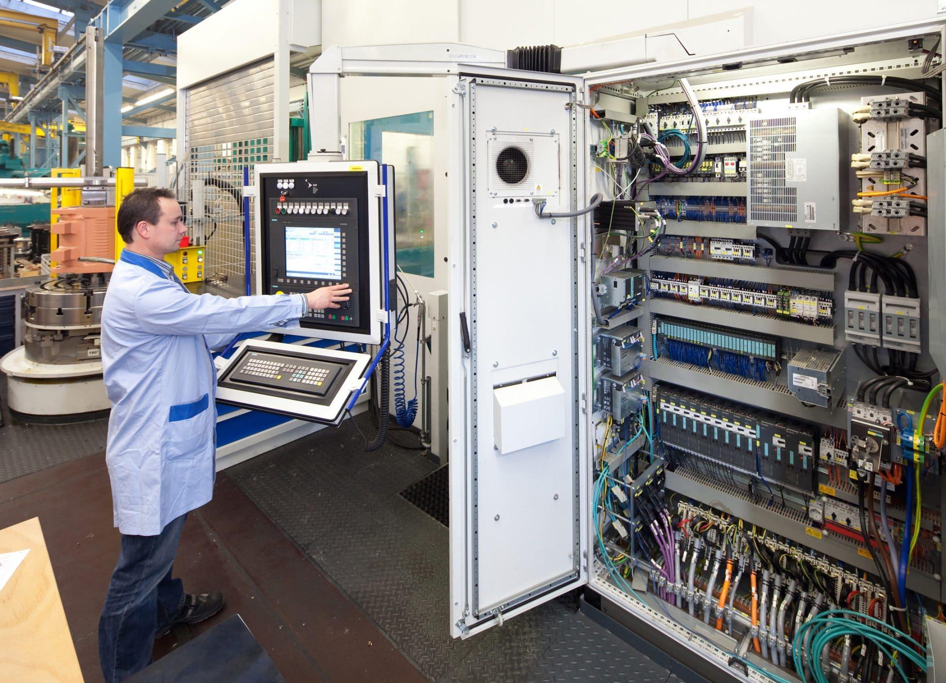 Servicetechniker beim Überprüfen der elektrischen Sicherung eines Dreh-/Fräszentrums.  Service technician checking the electrical protection of a machining/milling center.